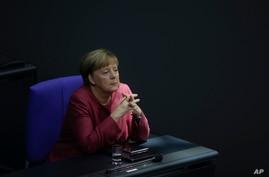 German Chancellor Angela Merkel listens to the debate about her policy as part of Germany's budget 2021 debate at the parliament Bundestag in Berlin, Germany, Sept. 30, 2020.