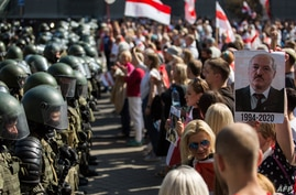 Belarusian security forces block a street during an opposition rally challenging official presidential elections results, in Minsk, Belarus, Aug. 30, 2020. The poster depicts President Alexander Lukashenko and the years he has been in power.