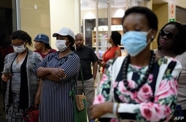 FILE - Customers wear masks to protect against the coronavirus while queuing at a supermarket in Gaborone, Botswana, March 31, 2020, during the early weeks of the country's COVID-19 restrictions.
