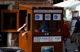 A ticket vendor for a canal boat tour operator waits in his booth in Bruges, Belgium, Aug. 24, 2020.