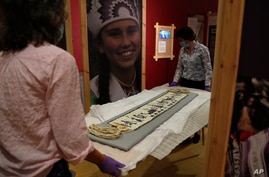 Co-curator Jo Loosemore, right, and Kate Johnson, Exhibitions Office Plymouth, prepare a recently created wampum belt made by members of the Wampanoag Native America people, to put on display in Southampton, England, Aug. 13, 2020.