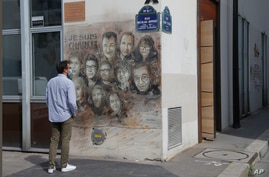 A man looks at a painting by French street artist Christian Guemy, a.k.a. 'C215' in Paris, France, Sept. 2, 2020, in tribute to the members of the satirical newspaper Charlie Hebdo attack by jihadist gunmen in Jan. 2015.