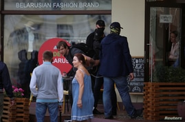 FILE - Unidentified men wearing face coverings detain a man near a cafe during an opposition rally challenging presidential election results in Minsk, Belarus, Sept. 6, 2020. (Tut.By via Reuters)