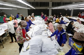 FILE - Employees work at a garment factory in Kandal province, Cambodia, Dec. 12, 2018.
