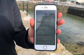 FILE - A National Health Service employee holds up a smartphone displaying a NHS app to trace contacts with people potentially infected with the coronavirus, on the Isle of Wight, Britain, May 5, 2020.
