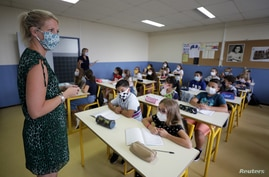 A teacher, wearing a protective face mask, teaches students in a classroom at the College Henri Matisse school in Nice, France, Sept. 1, 2020.