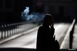 A man smokes a cigarette as he walks early morning in Frankfurt, Germany, Sept. 8, 2020.