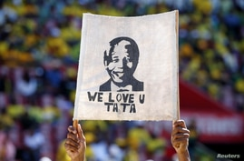 FILE - A supporter holds a placard with the face of the late Nelson Mandela, former President of South Africa, during the party's final rally at Ellis Park Stadium stadium in Johannesburg, May 5, 2019.