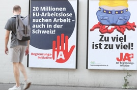 A man walks past posters of the Swiss People's Party (SVP) and of the Komitee Arbeitsplaetze fuer Einheimische schuetzen (committee to protect jobs for locals) against the anti-immigration initiative in Zurich, Switzerland, Sept. 17, 2020.