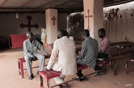 Lutheran reverend Yousef Zamgila (L) speaks to members of his congregation at the small improvised church they helped set up in…