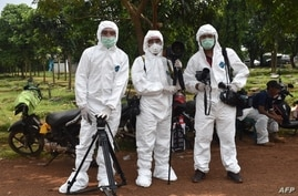 FILE - This picture taken with a self-timer shows AFP journalists in protective gear while reporting on a COVID-19 story at Pondok Ranggon cemetery in Jakarta, May 6, 2020.