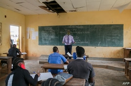 A teacher wearing a face shield as a preventive measure against the spread of the COVID-19 coronavirus teaches a class at the…