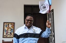 Tundu Lissu, the presidential candidate of Tanzania's main opposition Chadema party, poses with his party's flag as he speaks…