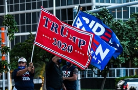 Supporters of US President Donald Trump and Democratic presidential nominee and former Vice President Joe Biden wave flags…