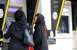 (FILES) In this file photo taken on May 20, 2019, Iranian women use automated teller machines (ATM) in Tehran. - US President…
