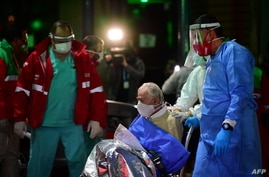 (FILES) In this file photo taken on May 07, 2020 an elderly man with symptoms of the new coronavirus is transferred from the…