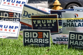 Trump-Pence and Biden-Harris signs are displayed outside The Coral Gables Branch Library in Miami, Florida on October 27, 2020…
