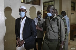 Terror suspect Mohamed Ahmed Abdi (L) and his co-accused, Hassan Hussein Mustafa (C) are escorted away after the ruling of…