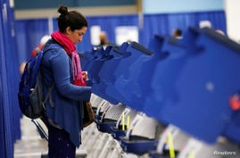 FILE - A voter casts her ballot during early voting in Chicago, Illinois.