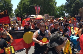 People carry Australian Aboriginal flags during a demonstration on Australia Day in Sydney, January 26, 2019. REUTERS/Stefica…
