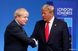 Britain's Prime Minister Boris Johnson shakes hands with U.S. President Donald Trump during a welcoming ceremony at the NATO…