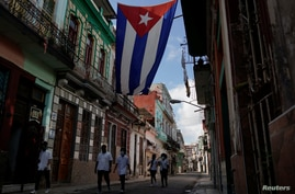 Medical students walk past a Cuban flag as they check door-to-door for people with symptoms amid concerns about the spread of…