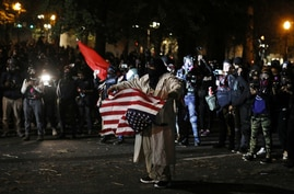 A demonstrator carries a U.S. flag during a protest against police violence and racial inequality in Portland, Oregon.