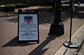 A sign is seen outside a mail ballot drop-off site after Gov. Greg Abbott issued an order limiting each Texas county to one…