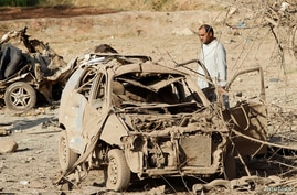 An Afghan man inspects the wreckage of a car at the site of a truck bomb blast in Ghani Khel district of Nangarhar province,…