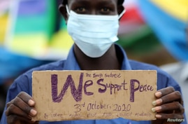 A civilian holds a placard as he celebrates the signing of peace agreement between the Sudan's transitional government and…