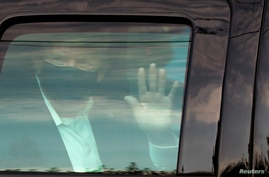 FILE - U.S. President Donald Trump waves to supporters as he briefly rides by in the presidential motorcade in Bethesda, MD.