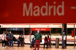 Commuters wearing protective face masks wait on a platform at Atocha train station during a partial lockdown amid the outbreak…