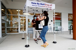 FILE - Katie Tricarico prepares to cast her mail-in voter ballot the last day of early voting for the U.S. election.