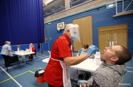 A health worker takes a swab from a man for COVID-19 test at a Stoke-on-Trent City Council facility at Fenton Manor Sports…