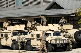 U.S. National Guard members are seen outside the Wisconsin State Fair exposition center where the U.S. Army Corps of Engineers…