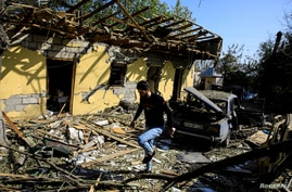 Residents search for their belongings at a restaurant hit by a shelling during the military conflict over Nagorno-Karabakh.