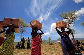 FILE PHOTO: Women from Dadinga tribe carry boxes of oil during food distribution by World Food Program (WFP) in the village of…