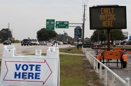 Signs are seen outside of a polling location during early voting in Sumter, South Carolina, U.S., October 9, 2020.  REUTERS…