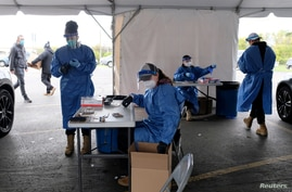 FILE PHOTO: Personnel administer coronavirus disease (COVID-19) tests in Milwaukee, Wisconsin, U.S., as cases spread in the…