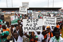 Supporters of Ivory Coast's Coast opposition coalition parties hold signs during a stadium rally to protest against president…