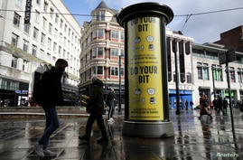 FILE PHOTO: A guidance sign is pictured following the outbreak of the coronavirus disease (COVID-19) in Manchester, Britain…