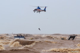 A military helicopter rescues sailors of a submerged ship at Cua Viet Port in Quang Tri province, Vietnam, Oct. 11, 2020.