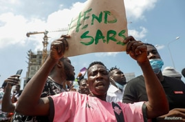 A demonstrator carries a banner during a protest over alleged police brutality, in Lagos, Nigeria, Oct. 12, 2020.