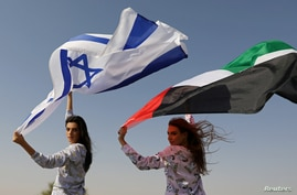 FILE - Israeli model May Tager, holding an Israeli flag, poses with Dubai-resident model Anastasia, holding an Emirati flag, during a photoshoot for FIX's Princess Collection in Dubai, UAE, Sept. 8, 2020.
