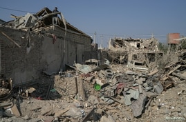 Ali Ibrahimov works on the ruins of his home, which was hit by a rocket, in the city of Ganja, Azerbaijan October 18, 2020…