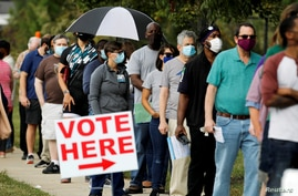 Voters wait in line to enter a polling place and cast their ballots on the first day of North Carolina voting.