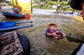 A boy gets food donation from a volunteer at a flooded area in Quang Binh province, Vietnam October 22, 2020. Picture taken…