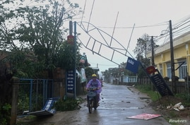 A man bikes past a broken sign as the Typhoon Molave lashes Vietnam's coast in Binh Chau village, Quang Ngai province October…