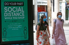 """Two women walk past a """"Social Distance"""" sign at City Creek Center Wednesday, May 6, 2020, in Salt Lake City. City Creek Center…"""