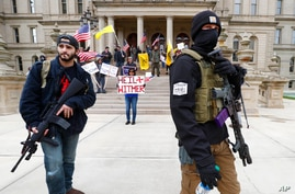 FILE - In this April 15, 2020, file photo protesters carry rifles near the steps of the Michigan State Capitol building in…